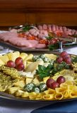 Assorted cheeses. Warious cheeses and ham on the plates Stock Photos