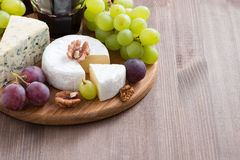 Assorted cheeses and fresh grapes on the board Royalty Free Stock Photo