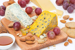 Assorted cheeses, grapes, crackers, honey and nuts on board Royalty Free Stock Photos