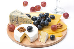 Assorted cheeses, grapes and glass of wine on wooden board. On white Stock Photos