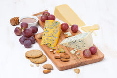 Assorted cheeses, grapes, nuts and crackers on a wooden board Stock Images
