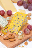 Assorted cheeses, grapes, nuts on cutting board Stock Images