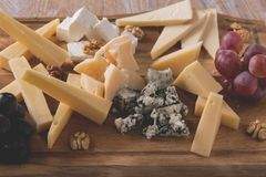 Assorted cheeses with grapes and walnuts on a serving board Royalty Free Stock Photography