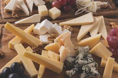 Assorted cheeses with grapes and walnuts on a serving board Royalty Free Stock Photo