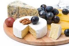 Assorted cheeses and grapes on a wooden board, isolated Stock Photos