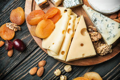 Assorted cheeses with nuts and dried fruits. On the table Stock Photo