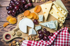 Assorted cheeses, nuts and grapes on a wooden table Royalty Free Stock Photo