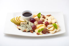 Assorted cheeses, pear, walnuts and grapes on a plate. On white background Royalty Free Stock Photos