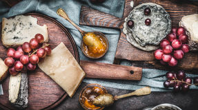 Assorted cheeses on rustic cutting boards with grape and honey mustard sauces Royalty Free Stock Image