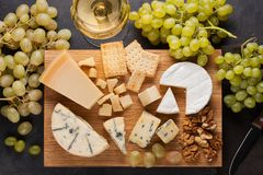 Free Assorted Cheeses With White Grapes, Walnuts, Crackers And White Wine On A Wooden Board. Food For A Romantic Date On A Royalty Free Stock Photography - 102599537
