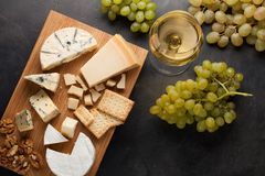 Free Assorted Cheeses With White Grapes, Walnuts, Crackers And White Wine On A Wooden Board. Food For A Romantic Date On A Dark Stone B Stock Photos - 102600173