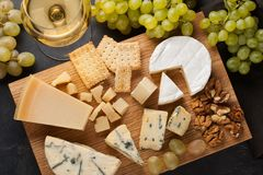 Free Assorted Cheeses With White Grapes, Walnuts, Crackers And White Wine On A Wooden Board. Food For A Romantic Date On A Dark Stone B Royalty Free Stock Photography - 102810077