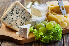 Assorted cheeses. On wooden board Stock Photography