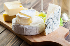 Assorted cheeses. On wooden board Royalty Free Stock Image