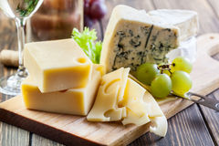 Assorted cheeses. On wooden board Royalty Free Stock Photos