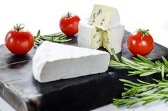 Assorted cheeses on wooden board. Camembert, cheese with blue mildew, mozzarella with tomatoes royalty free stock images
