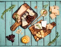 Assorted cheeses on wooden board plates served with nuts, grapes Royalty Free Stock Photos