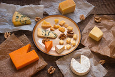 Assorted cheeses on the wooden table Royalty Free Stock Photos