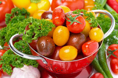 Assorted cherry tomatoes in a colander, garlic, spices and herbs Royalty Free Stock Images