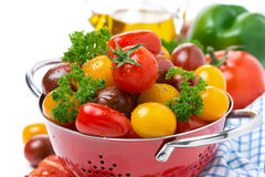Assorted cherry tomatoes and greens in a colander, close-up Royalty Free Stock Photography