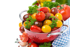 Assorted cherry tomatoes and greens in a colander, isolated Stock Photography
