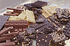 Assorted chocolate bars. Pile of assorted chocolate bars - heap of black and white chocolate pieces with hazelnuts Royalty Free Stock Image