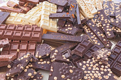 Assorted chocolate bars. Pile of assorted chocolate bars - heap of black and white chocolate pieces with hazelnuts Royalty Free Stock Photography