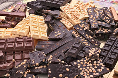 Assorted chocolate bars. Pile of assorted chocolate bars - heap of black and white chocolate pieces with hazelnuts Stock Image