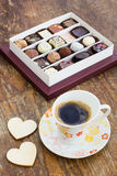 Assorted chocolate candies and cup of coffee on a wooden table Royalty Free Stock Image