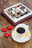 Assorted chocolate candies and cup of coffee on a wooden table Royalty Free Stock Photography