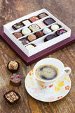 Assorted chocolate candies and cup of coffee on a wooden table Royalty Free Stock Images