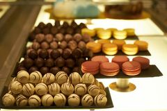 Assorted chocolate candies in a pastry shop, close-up. White chocolate nuts candy balls and macaroons, sweets dessert food royalty free stock photos
