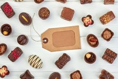 Assorted chocolate candies and price tag. Collection of chocolate sweets and blank vintage label on white wooden background. Confectionery sweet background royalty free stock photo