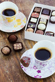 Assorted chocolate candies and two cups of coffee on a wooden ta Royalty Free Stock Images