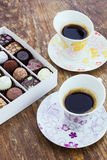 Assorted chocolate candies and two cups of coffee on a wooden ta Stock Photo