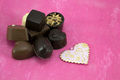 Assorted chocolates. Selection of assorted chocolates on a pink background Stock Image