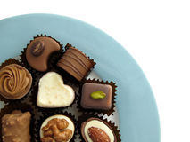 Assorted chocolates. On a blue plate isolated on white Royalty Free Stock Photo