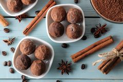 Assorted chocolates. candy balls of different types of chocolate on a blue wooden table. cocoa, cinnamon, star anise and coffee be. Ans. top view stock photo