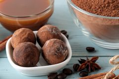 Assorted chocolates. candy balls of different types of chocolate on a blue wooden table. cocoa, cinnamon, star anise and coffee be. Ans royalty free stock images