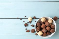 Assorted chocolates. candy balls of different types of chocolate on a blue wooden table. cocoa, cinnamon, star anise and coffee be. Ans. view from above. free royalty free stock images