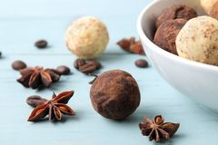 Assorted chocolates. candy balls of different types of chocolate on a blue wooden table. cocoa, cinnamon, star anise and coffee be. Ans royalty free stock image