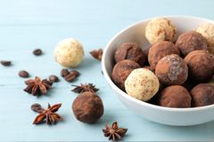 Assorted chocolates. candy balls of different types of chocolate on a blue wooden table. cocoa, cinnamon, star anise and coffee be. Ans stock photos