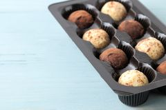Assorted chocolates. candy balls of different types of chocolate on a blue wooden table. free space. close-up stock photos
