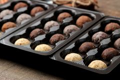 Assorted chocolates. Candy balls of different types of chocolate in a box on a brown wooden table stock image