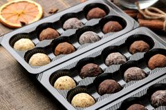 Assorted chocolates. Candy balls of different types of chocolate in a box on a brown wooden table stock images