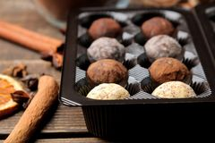 Assorted chocolates. Candy balls of different types of chocolate in a box on a brown wooden table stock photo