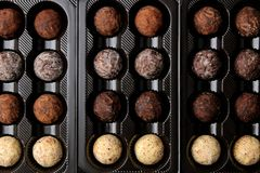 Assorted chocolates. Candy balls of different types of chocolate in a box on a brown wooden table. candy background royalty free stock photo