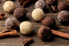 Assorted chocolates. candy balls of different types of chocolate on a brown wooden table. cinnamon and almonds stock images