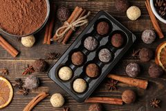 Assorted chocolates. candy balls of different types of chocolate on a brown wooden table. cinnamon and almonds. top view stock photos