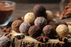 Assorted chocolates. candy balls of different types of chocolate on a brown wooden table. cinnamon and cocoa royalty free stock images